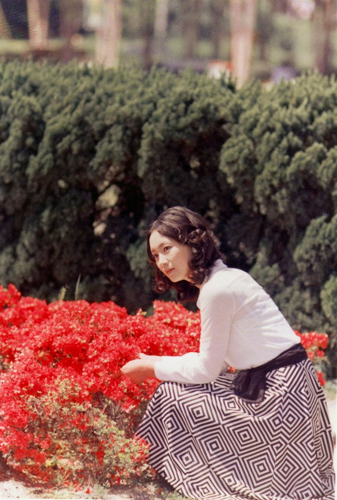 色鮮やかな花の前に座り込んむ島田陽子